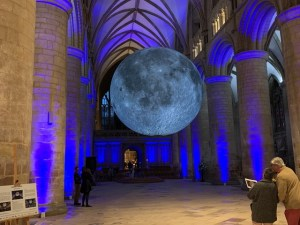 A cathedral auditorium. Large stone arches line the left and right sides and are lit with a blue glow. Suspended in the middle of the space is a large model or replica of the Earth's moon. Two groups of two people admire the moon.