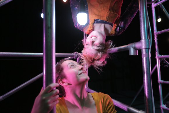 Two performers smiling at a hanging light.