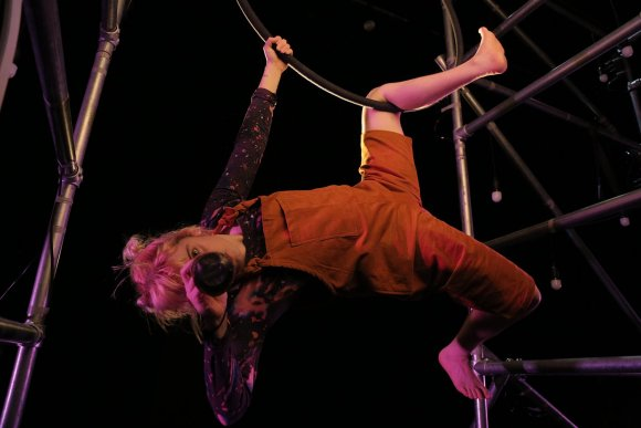 The performer, dressed in orange dungarees, hangs from a hoop whilst looking through a telescope at the camera.