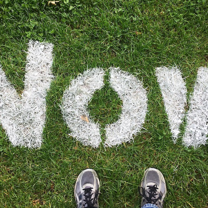 The word 'now' spraypainted on to grass