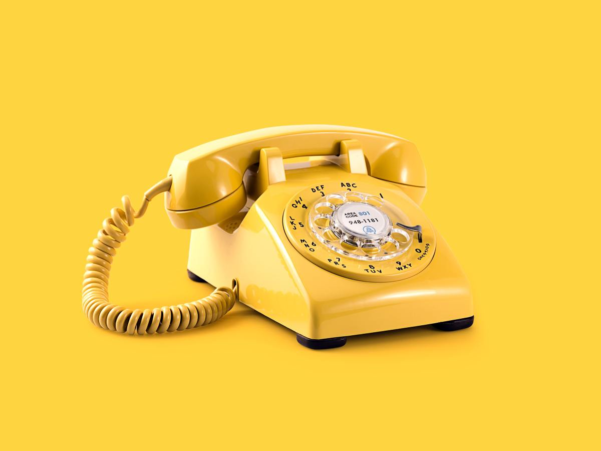 A yellow old fashioned telephone against a bright yellow background