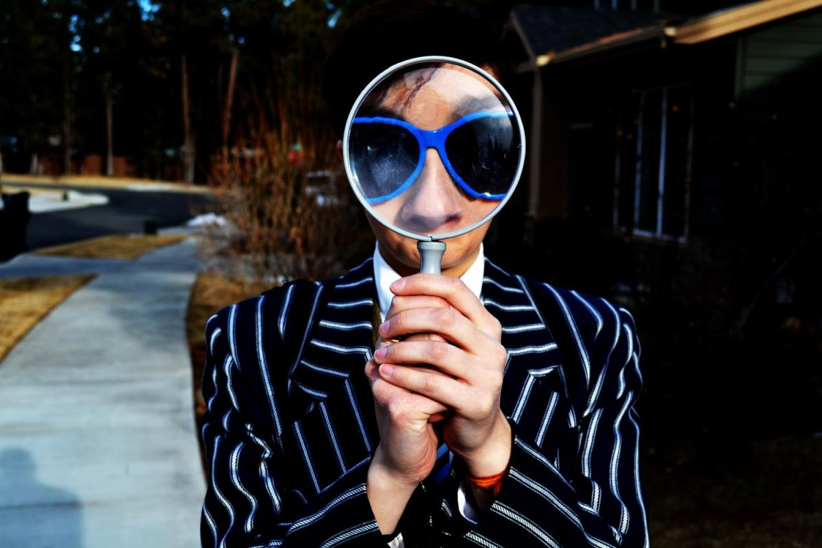 Person using magnifying glass, enlarging the appearance of their face