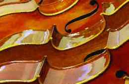 Cellos laying horizontally in a row