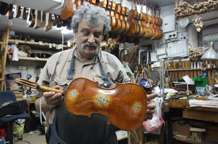 Amnon Weinstein in his shop with Violins of Hope