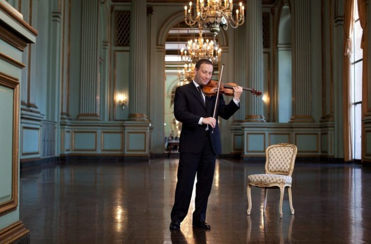 Violinist Tom Stone playing violin in a large room