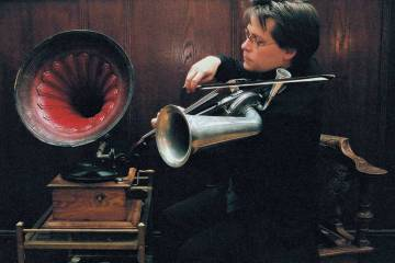 Man playing a stroh violin in front of a phonograph