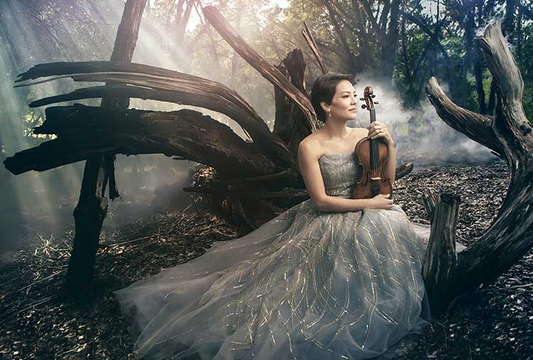 Anne Akiko Meyers in a white dress in the forest with a violin