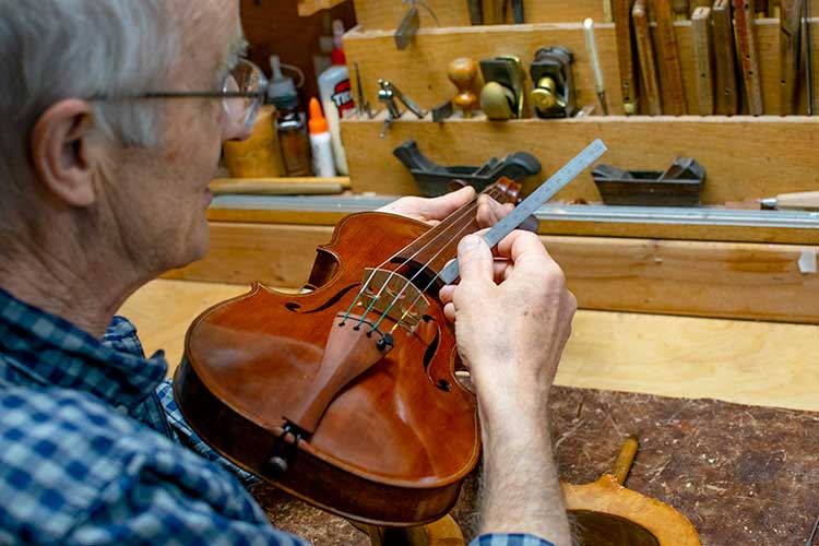 Andrew Carruthers holding Redwood Violin and small ruler
