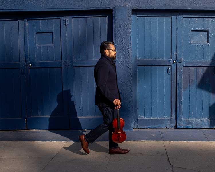 violinist Vijay Gupta walking with his violin against a blue wall
