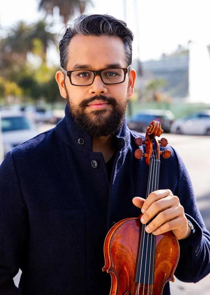 Vijay Gupta in a navy sweater holding his violin