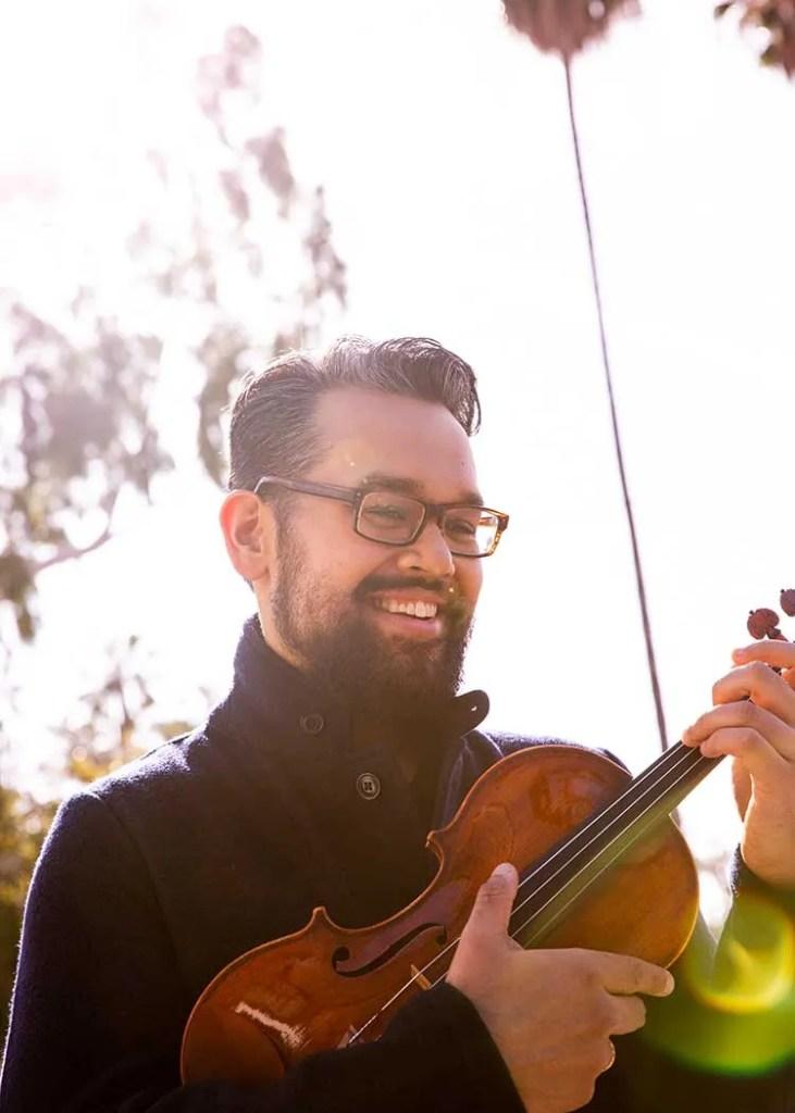 Vijay Gupta holding his violin outdoors