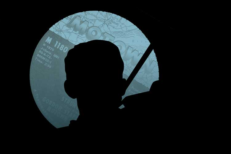 Violinist silhouted by motown record label black background