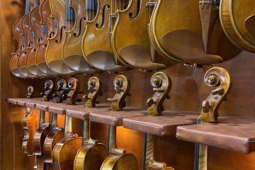 a row of violins hanging on display at Winter NAMM 2019