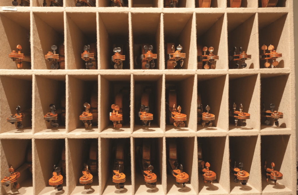 rows of violins stored away in cubbies for safety