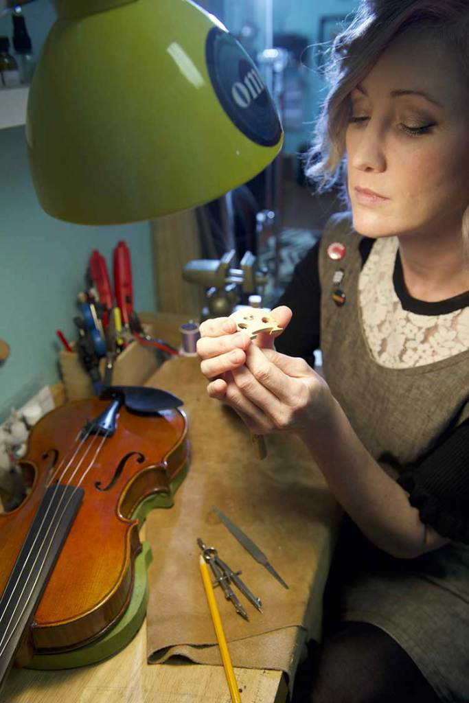 Luthier Rozie DeLoach inspects a violin bridge in her shop