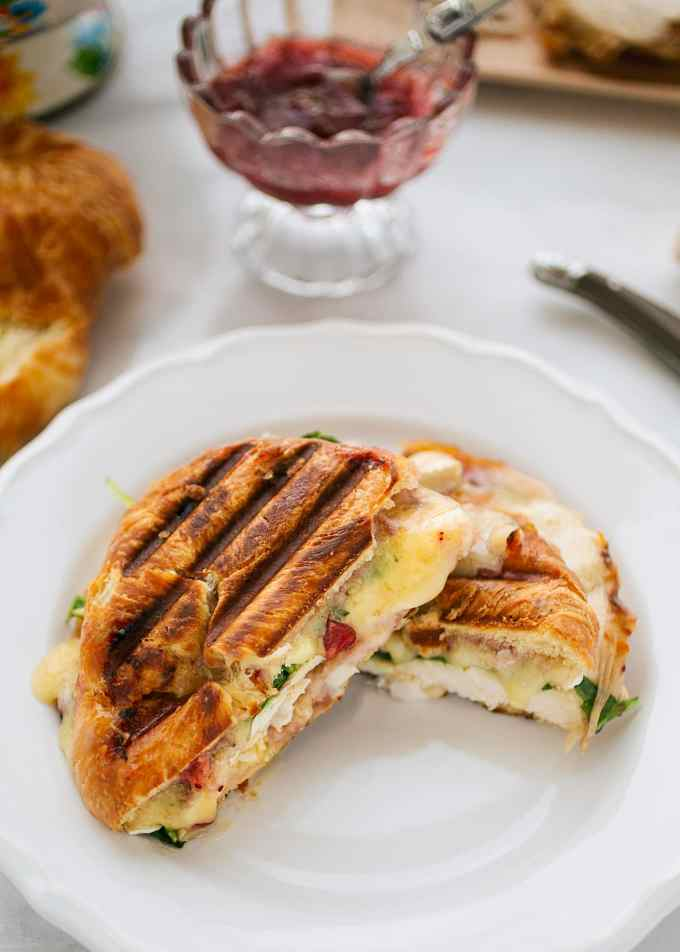 grilled turkey and brie croissant panini cut in half on a white plate
