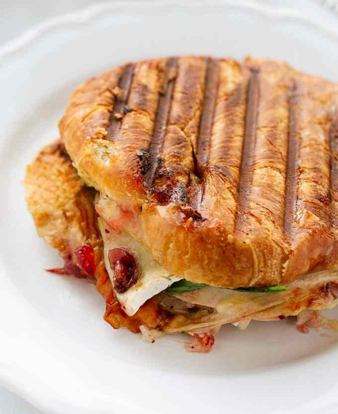 whole grilled turkey croissant panini on a white plate