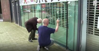 Robert van der Kroft en Marc Scherbateyev tekenen uit protest op de ruit van het stripmuseum Rotterdam.