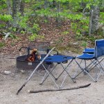 Campfire burning with chair, table and fire pokers ready