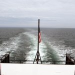 The American Flag flies on the back of the ferry boat