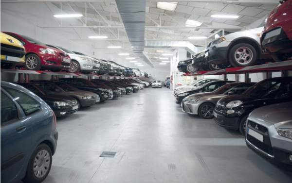 Large row of car lifts with cars on top and beneath them.