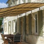 Light pergola above the entrance - an awning is stretched over a metal frame