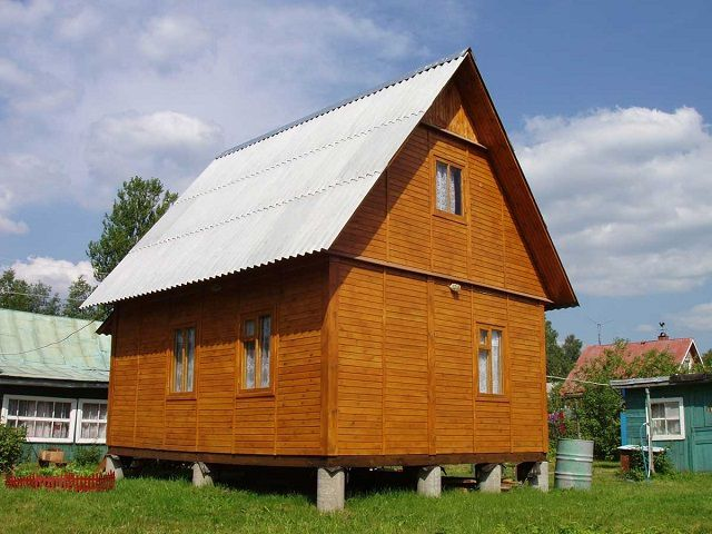 Maison en bois sur la fondation de la colonne de briques