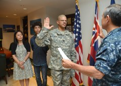 Army Maj. Anthony E. John, Command Safety Officer, USAR TSG-P reaffirms the commissioned officers oath of office right before he was officially pinned to his current rank by Adm. Harry B. Harris Jr., commander, U.S. Pacific Fleet, while his wife, Yuki, and son, Paul, look on during a promotion ceremony held at US PACFLT Headquarters, Pearl Harbor, Hawaii, on Nov. 25, 2013. (Photo provided by MC1 Amanda Dunford, PACFLT PAO)