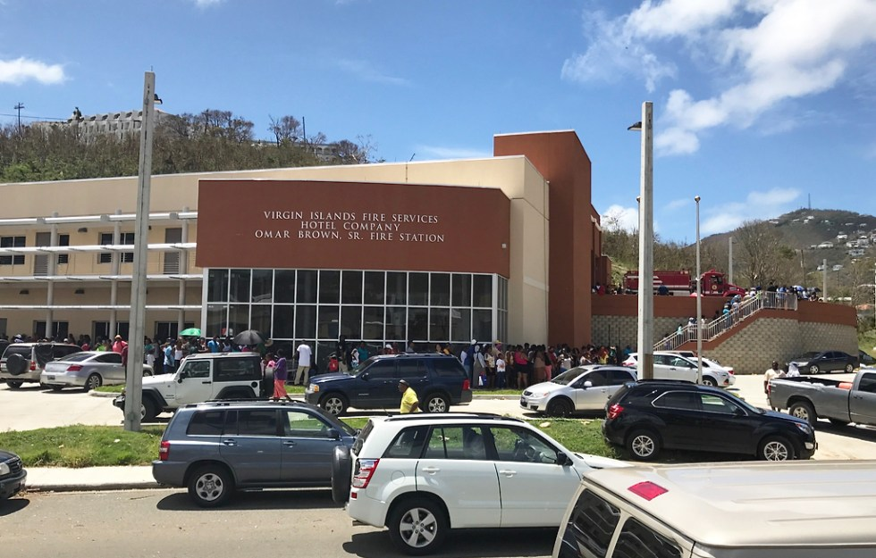 A line of St. Thomians wraps around the Hotel Company Omar Brown Fire Station Saturday. The station was designated a distribution center for relief goods. (James Gardner photo)
