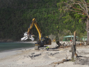 An earth-mover scoops up a load of debris at Magens Bay.
