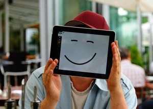 Man with smiley face drawn on I pad