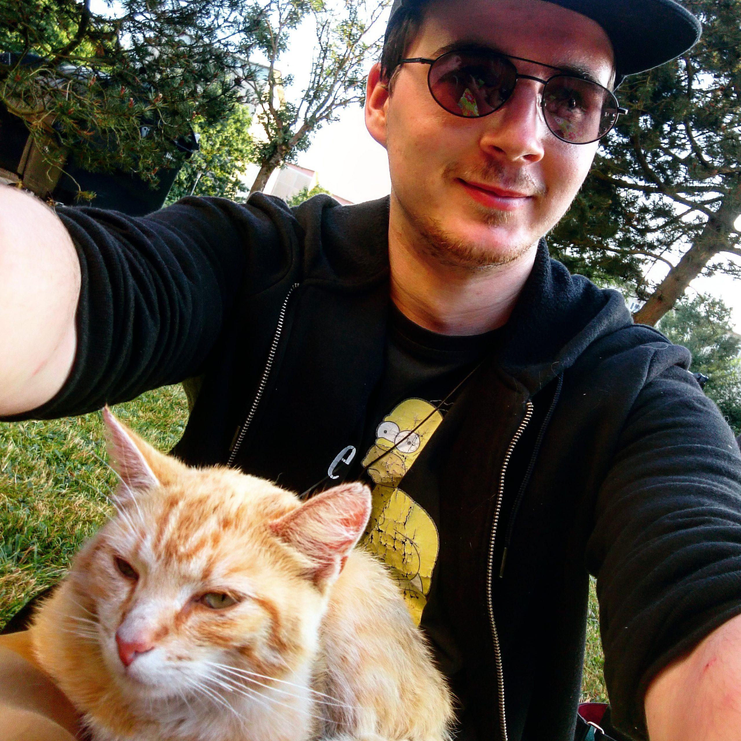 Felix T. Vogel sitzt mit einer Sonnenbrille und Katze auf einer Wiese