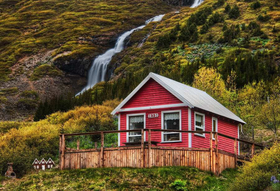 """Little Elves, Little WaterfallGoing into one of the valleys by Isafjordur takes you to many little homes near waterfalls.  I thought this one was quite lovely.And if you look to the left there, you'll see the tiny homes they also built for the elves.I was editing this photo at dinner one evening in Isafjordur.  One of the waitresses saw this house, recognized it, and said, """"Oh that's jklasdj(jkasdj^dhsaj"""".  Of course, I am doing my best to approximate the Icelandic language there...- Trey RatcliffRead the rest here at the Stuck in Customs blog."""