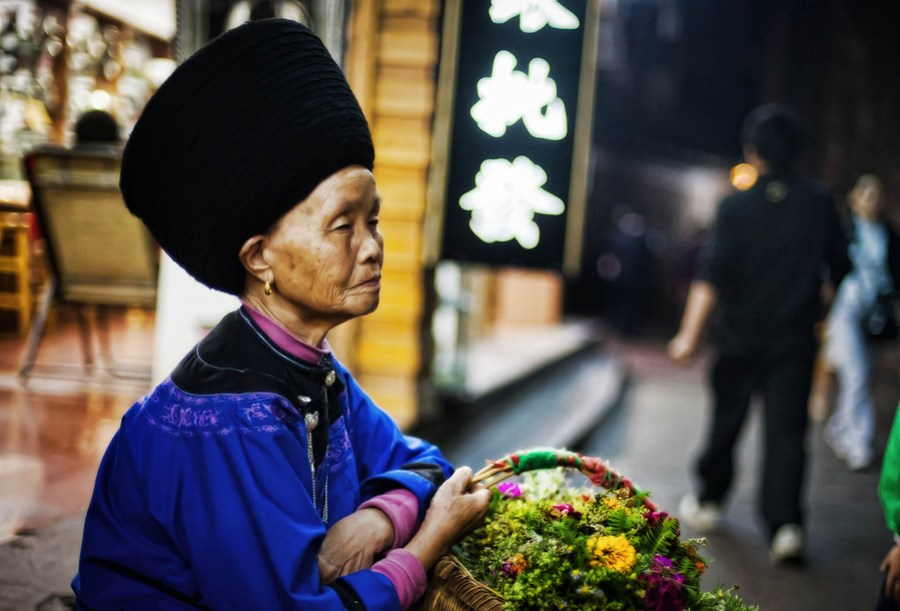 Selling Flowers in South China It was a wet, humid, but cool night when I was walking through Feng Huang.  It was one of those nights where you are not sure if you want to wear a sweatshirt or just something light.  Wearing something heavy holds the threat of getting moist and making you more uncomfortable… wearing something light holds the threat of keeping you too cold.I saw this lady selling flowers on the side of the road.- Trey RatcliffClick here to read the rest of this post at the Stuck in Customs blog.