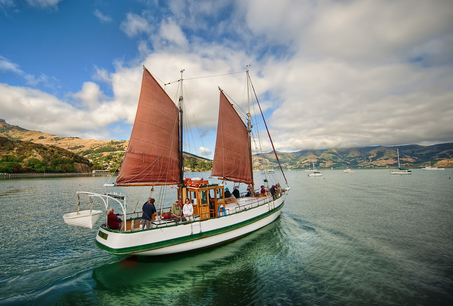 Sailing Away to AkaroaThanks again for all the recommendations!  So many of you recommended that we visit Akaroa on our visit to New Zealand, and it was a great suggestion.You can walk along and see most of the commercial part and the harbor in less than an hour.  One end is a long dock where they launch a few ships per day.  Just as I got out to the end, this sailboat was pulling away from the dock.This photo came from a single RAW file.  There was way too much movement to let me do a multiple exposure in this one.- Trey RatcliffClick here to read the rest of this post, including info on the podcast, at the Stuck in Customs blog.