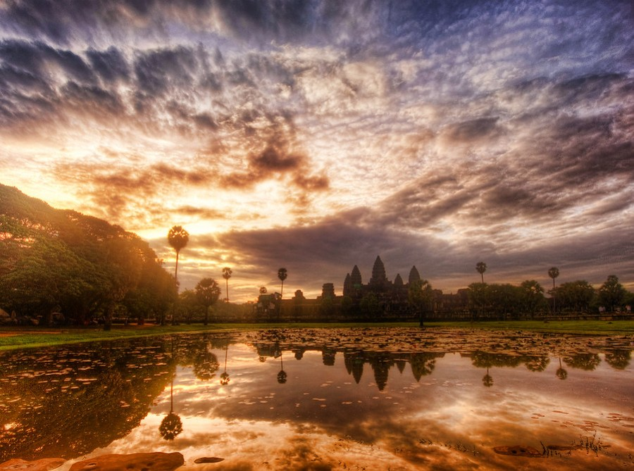 Colorful Cambodia Many of my Cambodia photos ended up going in more of the monochromatic direction.  I like the black & white look + sepia treatments.  They make it all seem sort of timeless and nice.  But when I was processing this one, I decided to have the sunrise colors shine through.I remember at this point in the morning, my lens was finally fog-free.  This was a hard lesson to learn, but now I no longer go from AC environments to muggy outdoors in the same way.  If I have to go through this situation, I normally keep my camera inside a big ziplock baggie, which ends up getting most of the condensation when I go back outside.- Trey RatcliffClick here to read the rest of the post at the Stuck in Customs blog.
