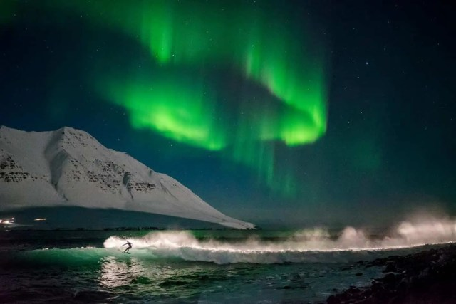 Surfing Iceland under the northern lights, deep in the Westfjords! Photo by Chris Burkard.