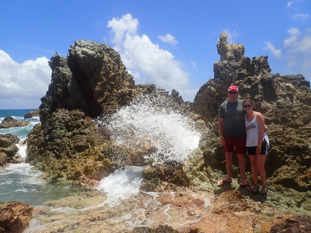 Water shooting through a geyser hole that Tyler & Anna are standing next to.