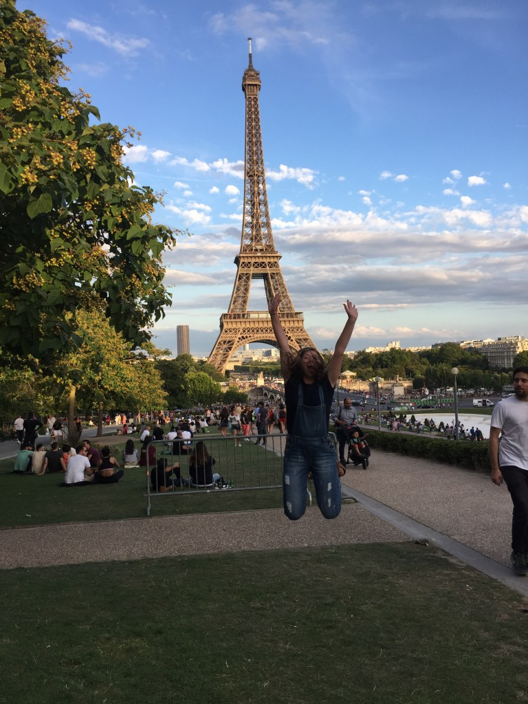 Girl jumping in front of the Eiffel Tower.
