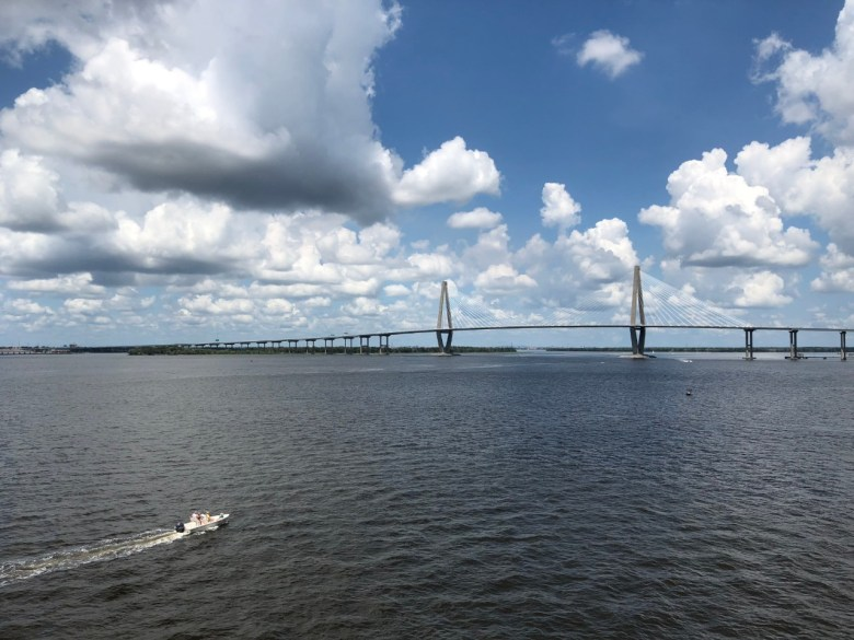 The Ravenel Bridge that spans the Cooper river in Charleston, SC. A beautiful blue-bird day with a boat on the water.