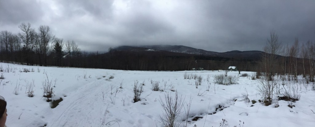 A look back on the mountain at Smugglers' Notch while snowshoeing. The sky is overcast and foggy.