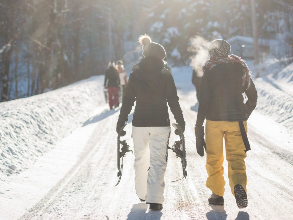 A couple walking with their snowshoes to the slopes. Something you'll see at Smugglers' Notch.
