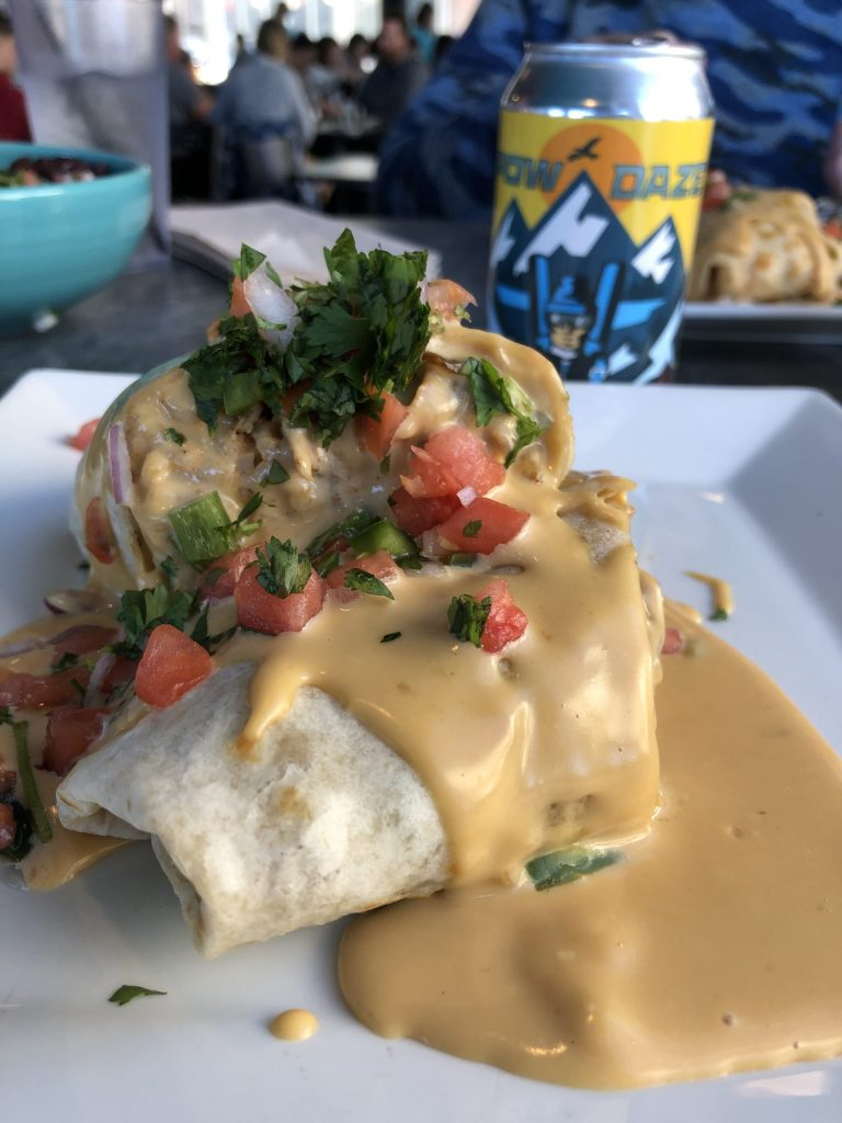 The chicken burrito from Sunset Cantina in Snowshoe, West Virginia. The burrito is smothered in cheese and topped with diced tomatoes and parsley.