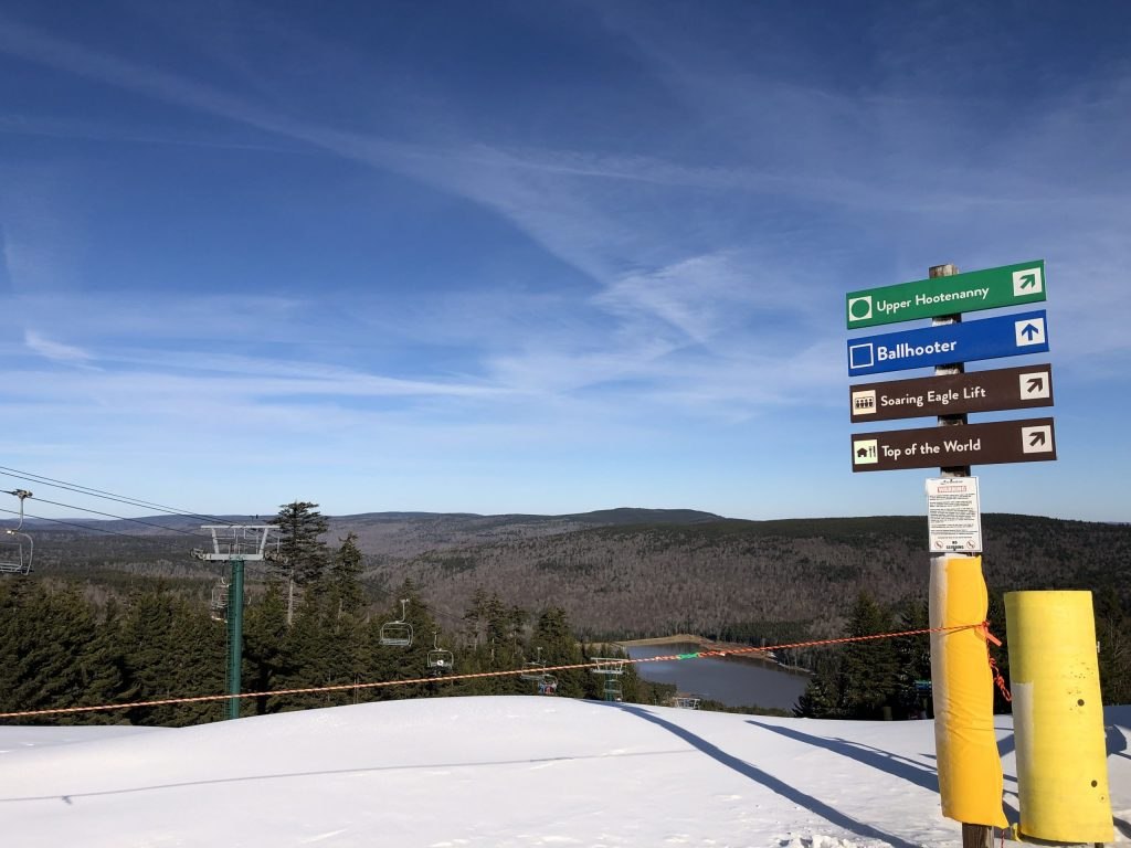 The top of Ballhooter lift at Snowshoe, West Virginia on a bluebird day with the lake visible below.