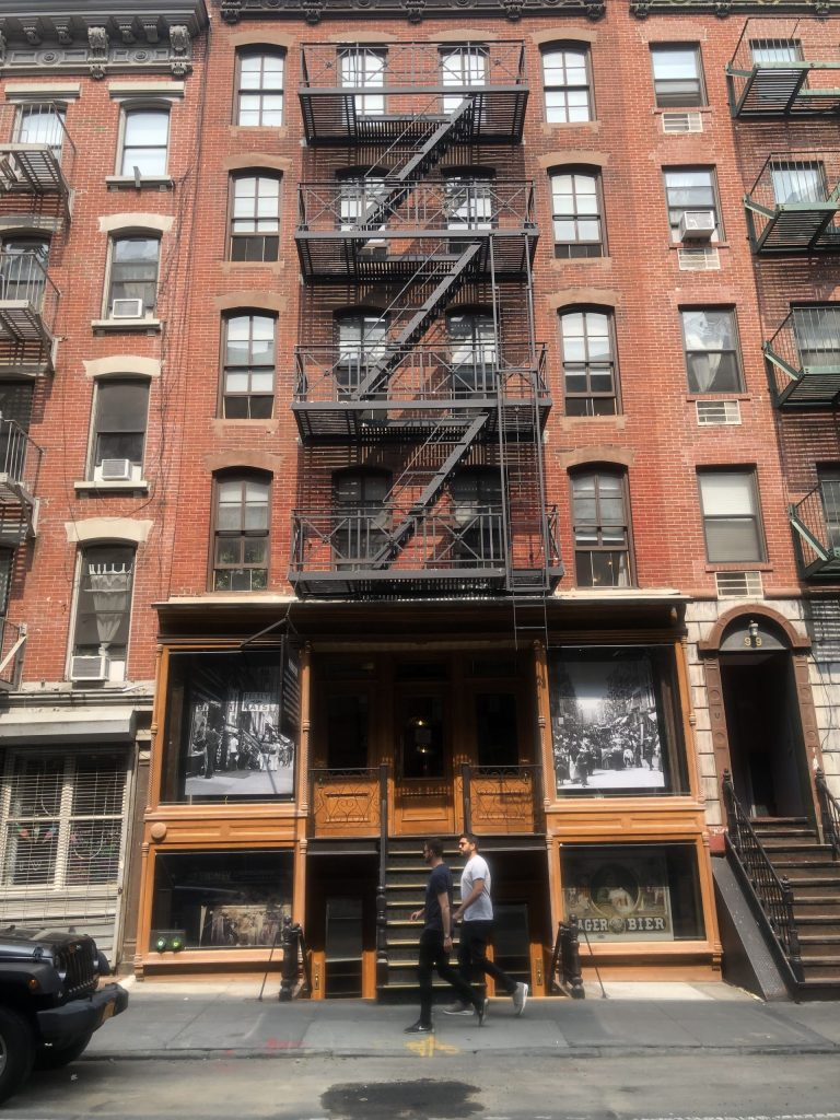 The outside of a brick apartment building with a fire escape. The Tenement Museum should be on your weekend in New York City Itinerary.