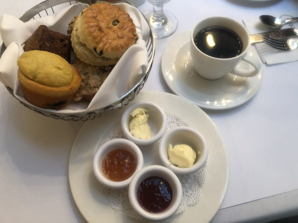 A basket of muffins with butter and jam and a cup of coffee. Brunch is a must during your weekend in New York City.