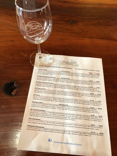 Dobbins creek vineyard tasting menu with wine glass beside it