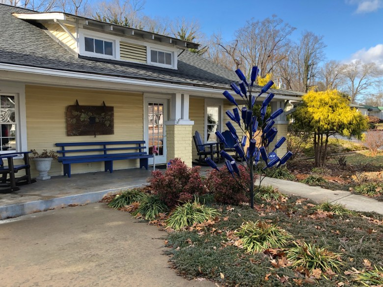 yellow building with front porch and blue bottle tree outside. slightly askew - best yadkin valley wineries.