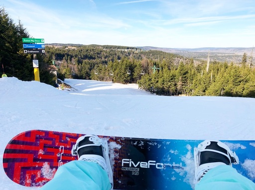 Snowboard sitting in front of a ski slope and sign. Is snowboarding hard?