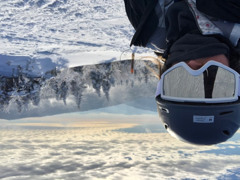 Girl with snowboarding helmet and goggles on and mountain ridges in the background. Is snowboarding hard?